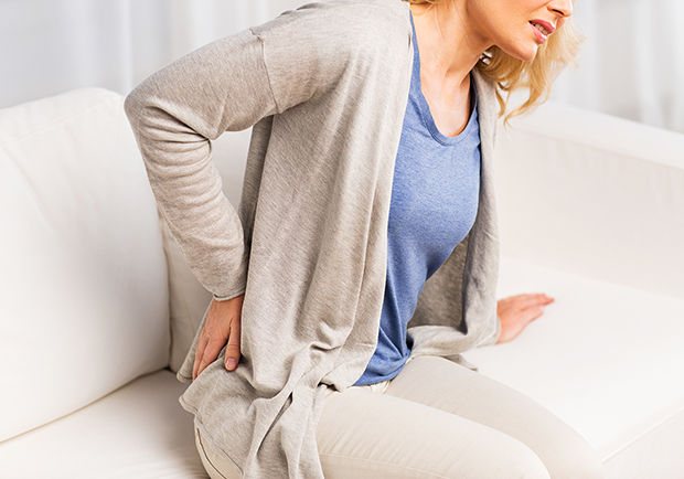 Woman on couch with back pain, way's to alleviate back pain