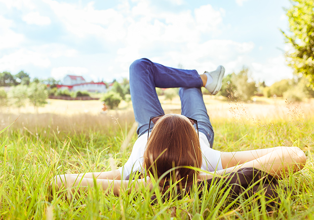 Woman relaxing in the grass, how to relieve stress and anxiety