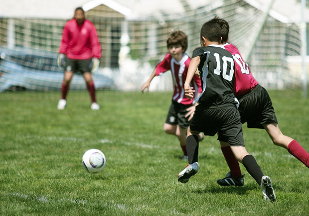 Kids playing soccer outside, help your kids develop healthy habits