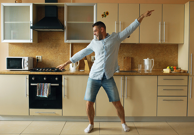 Man in kitchen dancing, staycations