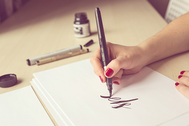 Woman writing in calligraphy on a piece of paper
