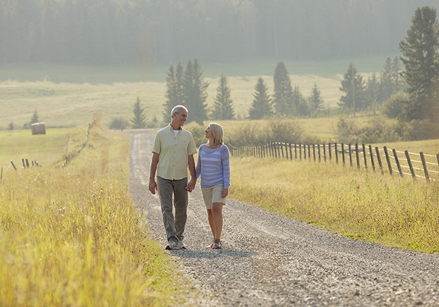 Older couple walking down a path, practicing low-impact workouts