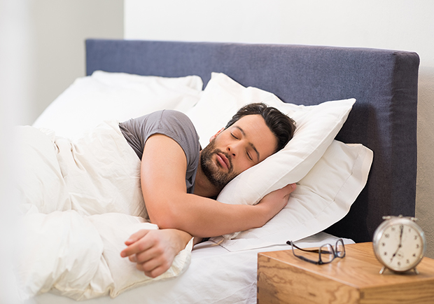 Man sleeping in bed, how does sleeping help with weightloss?