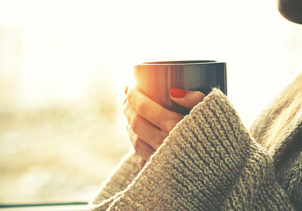 Woman holding a cup of coffee, coffee benefits