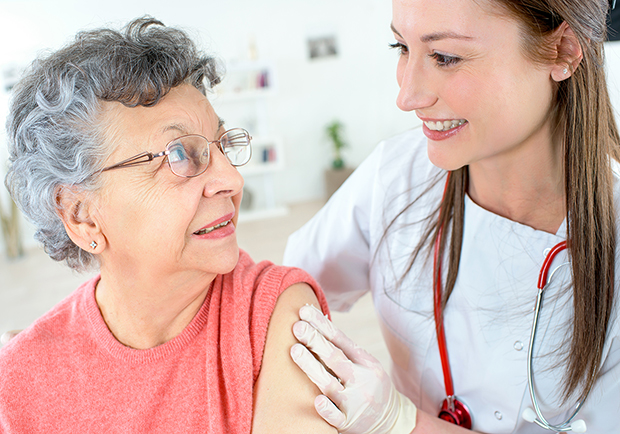 Nurse giving older woman a flu shot