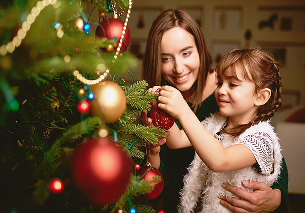 Mom and daughter decorating a tree, tips for de-stressing your holidays