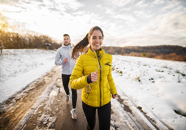 Woman and man running outside, tips for staying fit during the cold months