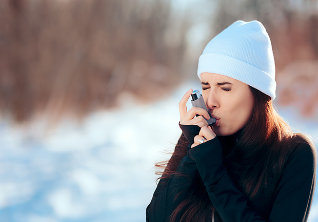Woman with inhaler dealing with asthma during the winter, large