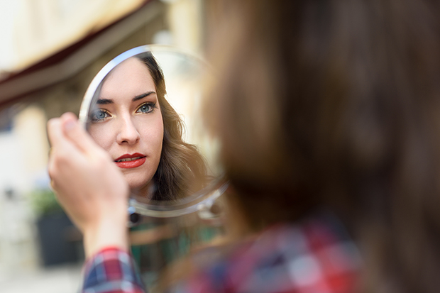 Woman looking in mirror, positive self talk