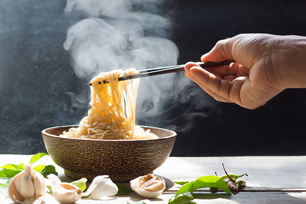 Hand eating noodles with chopsticks, healthy eating around the world