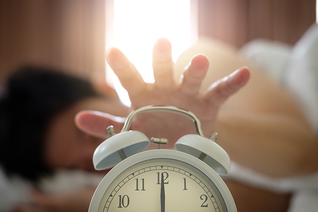 How to become a morning person, woman reaching for alarm