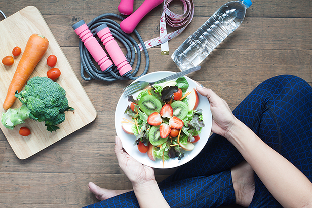 woman holding a healthy plate of food and exercising, ways to help prevent cancer