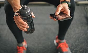 Using your phone to track your fitness, man looking at phone