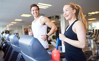 Happy couple on treadmills, take advantage of our gym reimbursement program