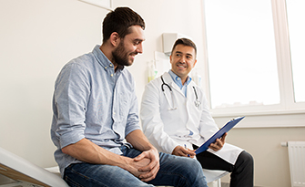 Man sitting with a doctor getting a preventive exam, small