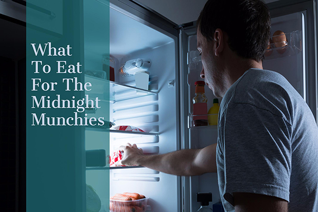 Man looking into a refrigerator reaching for a snack, midnight munchies