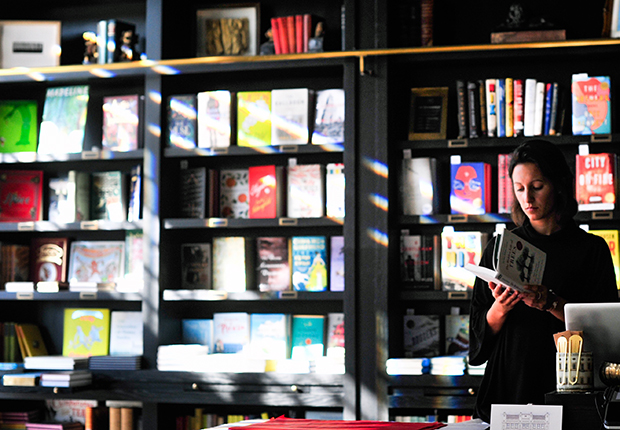 Woman stands in front of a booshelf reading a book