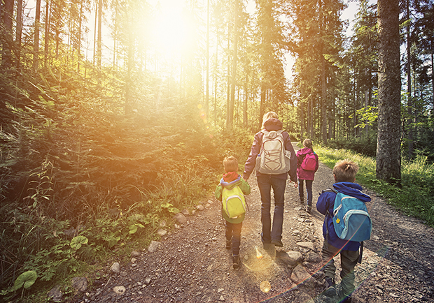 Family walking through the woods with backpacks on