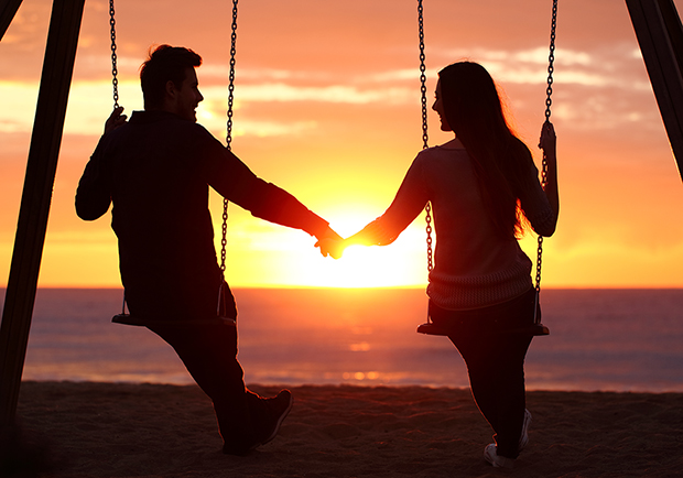 Man and woman holding hands on a swing set, learn how to strengthen relationships