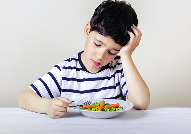 Child eating carrots and peas, how to help picky eaters
