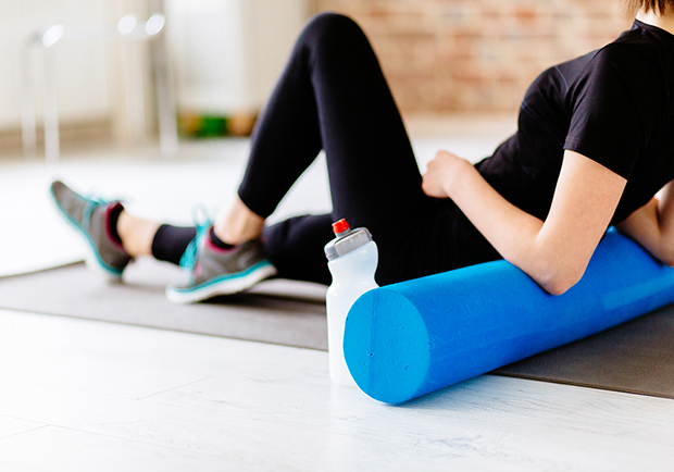Woman using a foam roller after a workout, learn what the benefits to foam rolling are