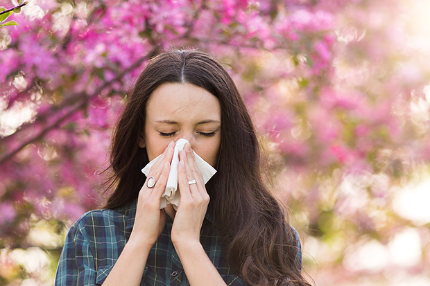 Woman blowing her nose, symptoms of Hay Fever