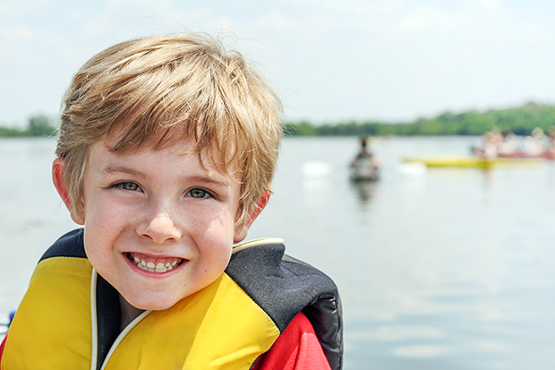 Child in life jacket, water safely in open water