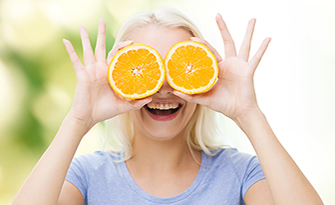 Woman holding orange slices, eye health sm