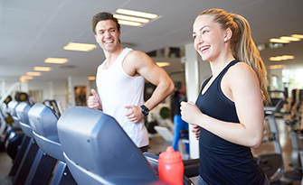 Happy couple on treadmills, take advantage of our gym reimbursement program